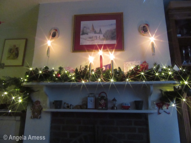 Photo of Christmas lights and candles on mantle piece